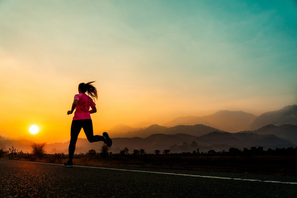 A woman enjoying her run in the morning while the sun is rising.